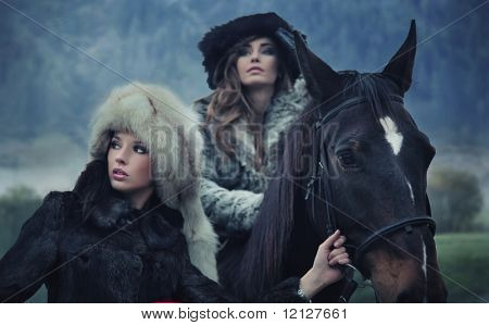 Two sensual female beauties posing with a horse
