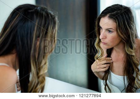 thoughtful woman inspecting her appearance in the bathroom mirror