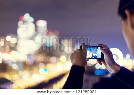 smartphone with cityscape and night scene of seattle at night