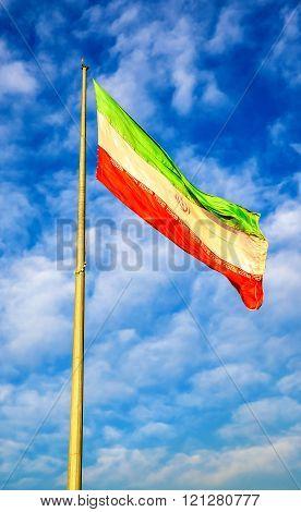 Iran flag against blue sky