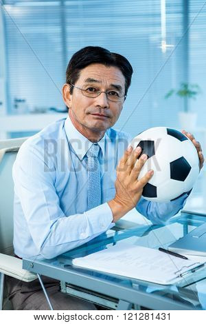 Asian businessman holding soccer ball in an office