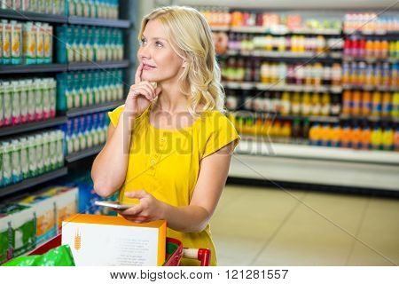 Thoughtful woman with trolley at supermarket