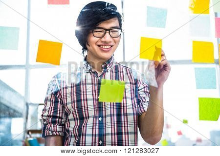 Creative businessman writing on sticky notes in office