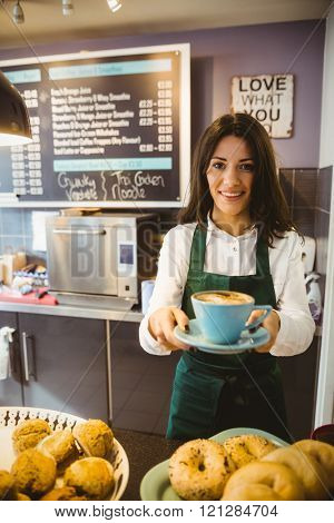 Waitress serving a cup of coffee in cafe