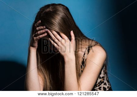 Sad woman covering her face with hands