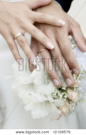 Wedding bouquet from white and pastel pink flowers, hands and rings