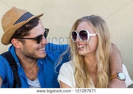 Hip couple with sunglasses smiling to each other