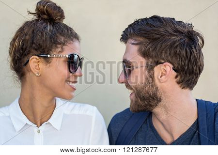 Hip couple with sunglasses looking at each other