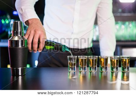 Bartender pouring cocktail into shot glasses at bar counter in bar