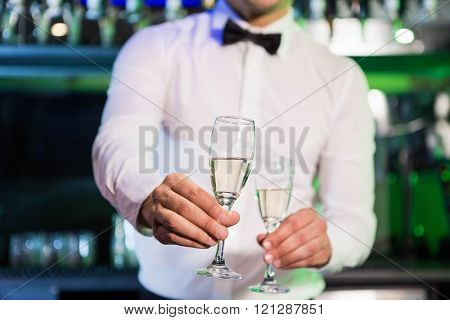 Bartender serving glass of champagne at bar counter in bar
