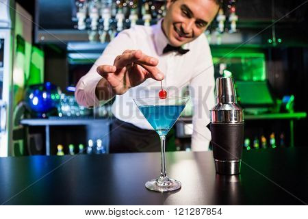 Bartender garnishing cocktail with cherry on bar counter in bar