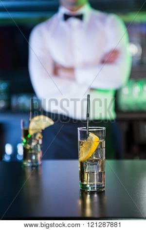 Two glasses of gin on bar counter and bartender standing in background