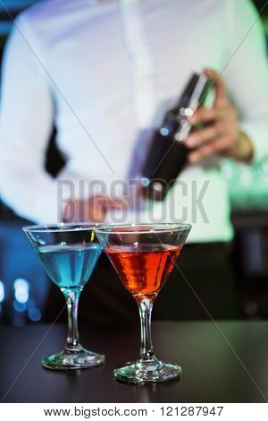 Two glasses of cocktail on bar counter and bartender holding shaker in background
