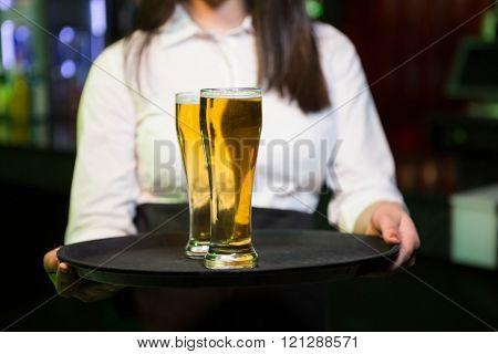 Bartender serving two glasses of beer in bar