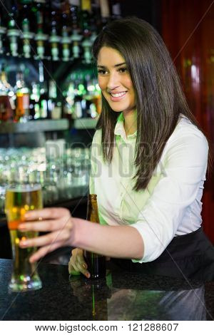 Pretty bartender serving beer at bar counter