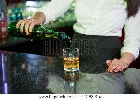 Bartender pouring whiskey in a glass at bar