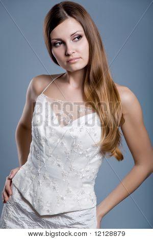 Slim beautiful woman with long hair wearing luxurious wedding dress over gray studio background