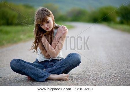 Jovem cansada com olhos fechados, sentar-se na estrada
