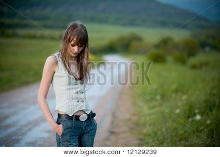 Young lonely woman with wet hair staying on road dropping down her head