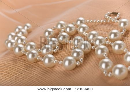 Necklace with big pearls on beige background