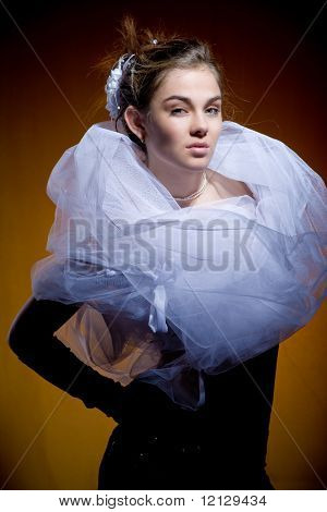 Beautiful glamour model on brown background in eccentric dress
