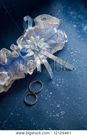 Wedding rings lying near garter on blue textile background