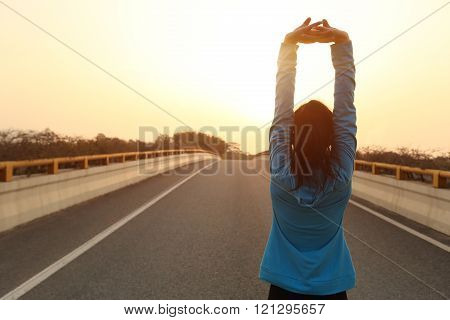fitness sports woman runner stretching on sunrise city road