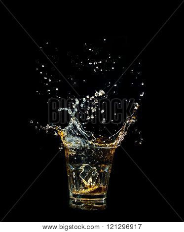 Whiskey splash in glass isolated on black background.