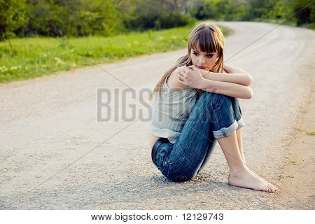 Sad girl sitting down on road
