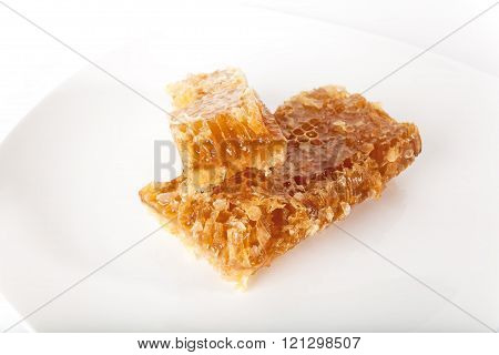 Honey comb on the plate over white background