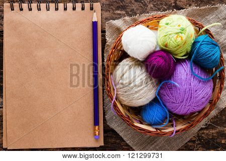Notebook, A Pencil And A Basket With Balls Of Yarn