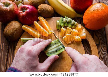 Man Cuts Fruit On A Cutting Board