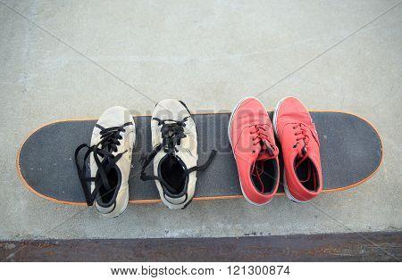 closeup of sneakers on skateboard at skatepark ramp