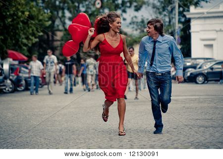 Running happy teenage couple in street