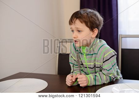 Little 7 years old boy holding fork and knife and waiting for dinner