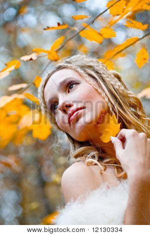 Portrait of beautiful blond bride holding yellow leaf near autumn tree