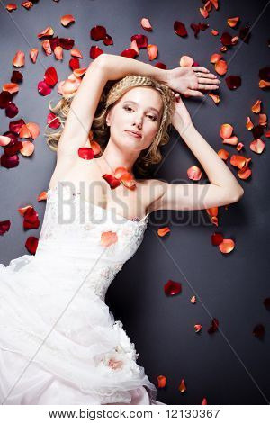 Beautiful sexy bride lying on the floor among red rose petals on gray background