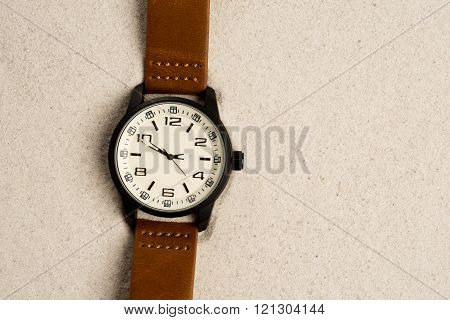 Watch with leather strap on sand background