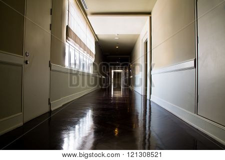 Dark, empty, mysterious corridor with available natural light from window