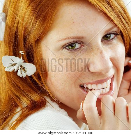 Photo of beautiful young girl with red hair and freckled skin on her face, square composition