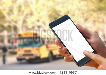 hand holding smartphone against schoolbus on ny street