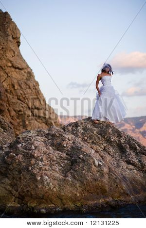 Bride in fashion wedding dress posing on mountain over sea