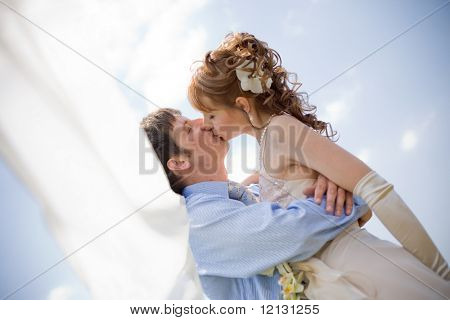 Kissing wedding couple over sky