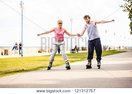 Young couple rollerblading in park