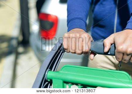 Closeup picture of male hand holding shopping push cart on car parking