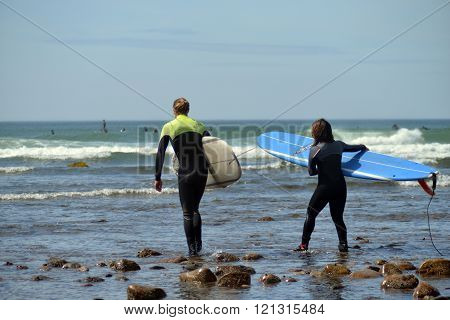 NEW YORK-JUNE 13: Unidentified women surfers with surfboard on Ditch Plains surfing beach go to surf in Montauk New York in the Hamptons on June 13 2015.