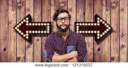 Confident hipster wearing eye glasses with arms crossed against wooden planks background