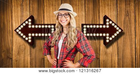 Gorgeous smiling blonde hipster with hands on hips against wooden background