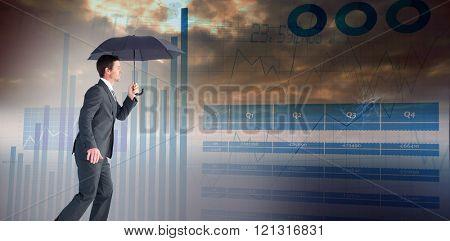 Businessman sheltering under black umbrella against blue data