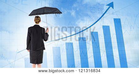 Businesswoman holding a black umbrella against blue data